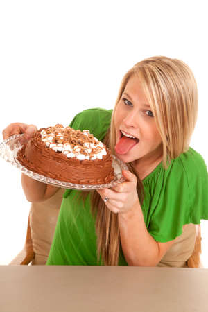 a woman holding on to her chocolate cake, getting ready to lick the frosting. photo