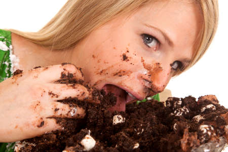 A close up of a woman shoving her face with chocolate cake. photo