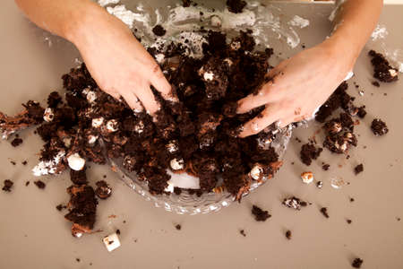 mess: A womans hands in a cake making a mess.