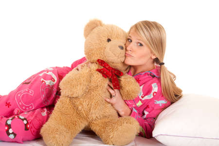 one sheet: a woman in her pink pajamas holding onto her teddy bear. Stock Photo