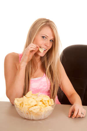 snacking: a woman in her chair, snacking on her potato chips.