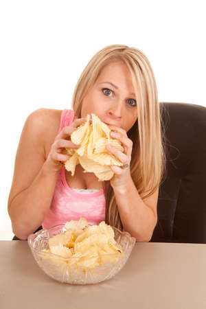 a woman stuffing her face with potato chips. photo