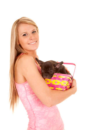 A woman holding on to her Easter suprise a puppy in her basket. photo