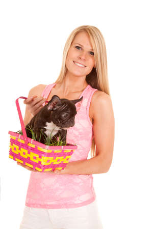 a woman holding on to her Easter basket with a puppy in it. photo