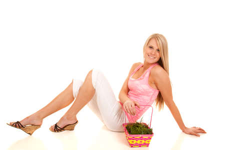 A woman sitting on her butt next to her easter basket. photo