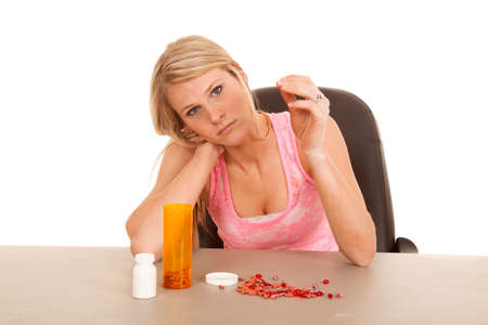 a woman with pills laying on a table looking sad. photo