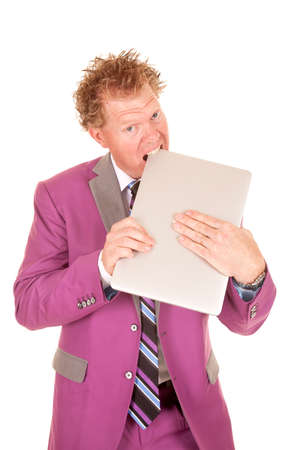 A man in a purple suit and wild hair biting his laptop. photo
