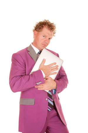 a man in a purple suit holding on tight to his laptop. photo
