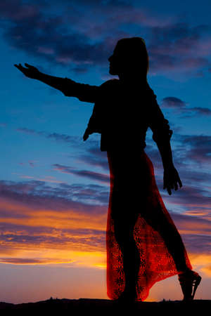 A silhouette of a woman in her dress reaching out.