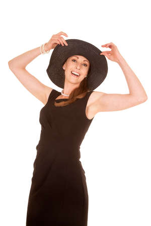 a woman standing with a big smile playing with her hat. photo