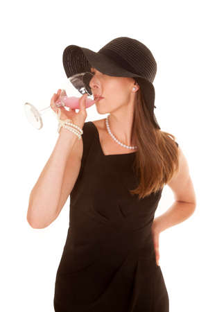 A woman in her black dress, taking a drink out of her cup. photo