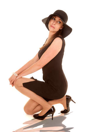 a woman kneeling down in her black dress and black floppy hat.