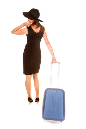 A woman in her black dress pulling on her suitcase going on a trip. photo