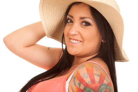 A woman with a hat looking with a tattoo on her shoulder. photo