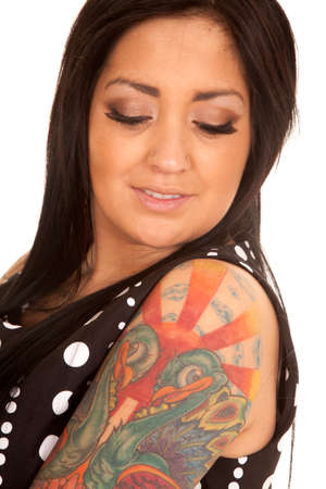 A woman in her polka dot dress looking down at her tattoo. photo