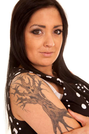 a close up of a womans tree tattoo with a serious expression on her face. photo