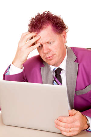 A man in his purple suit looking frustrated while working on his computer.