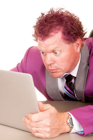 a man in his purple suit with big eyes looking at his laptop. photo