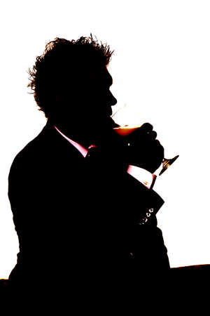 A silhouette of a man getting a drink from a glass. photo