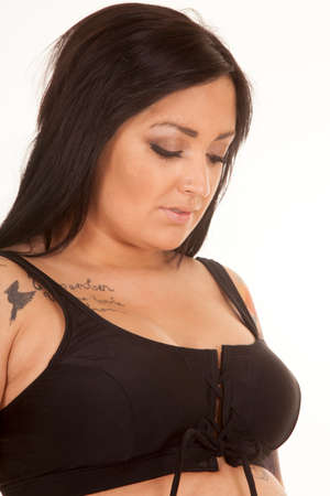 a woman in her bikini with tattoos on her chest and shoulder. photo
