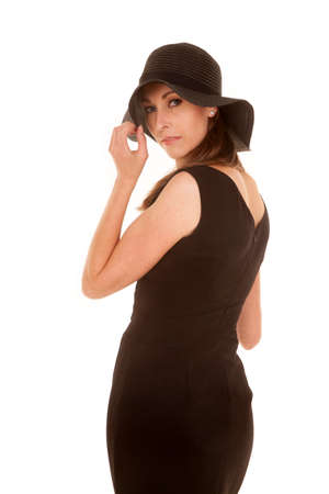 a woman in her black dress touching the brim of her hat. photo