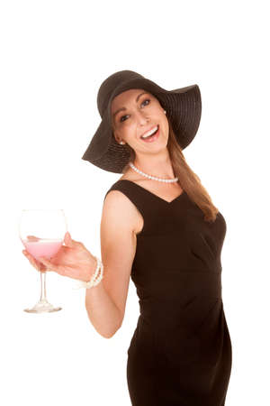 a woman in her black dress holding on to a glass wearing a hat and laughing. photo