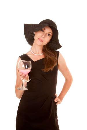 a woman in her black dress and hat holding onto  a glass filled with a drink. photo