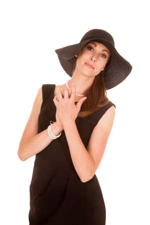 a woman with her hands up by her neck wearing her floppy black hat. photo