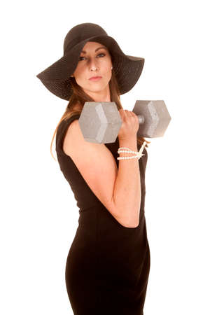 a woman in her black dress working out with  a big weight. photo