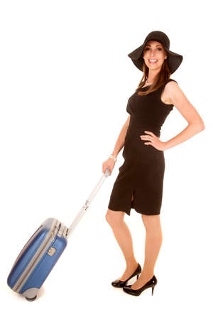 A woman inher black dress and hat with luggage ready to go on a trip. photo