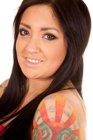 A close up of a woman looking with a tattoo on her shoulder. photo