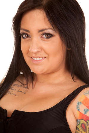 A close up of a woman  with a smile showing off her tattoos. photo