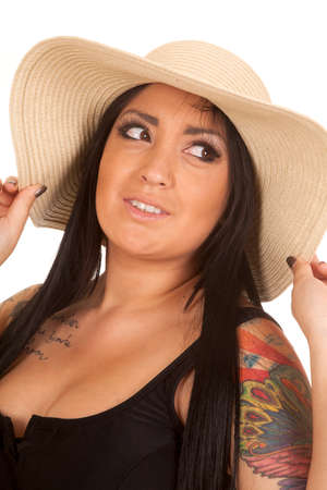 A woman in her big hat and tattoos on her shoulder. photo