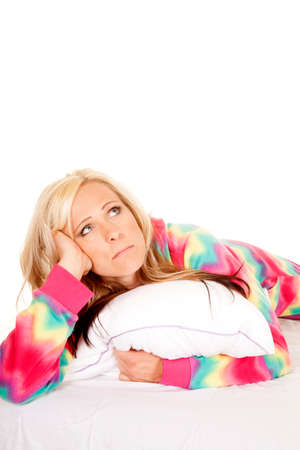 A woman in her colorful pajamas holding on to her pillow looking up. photo