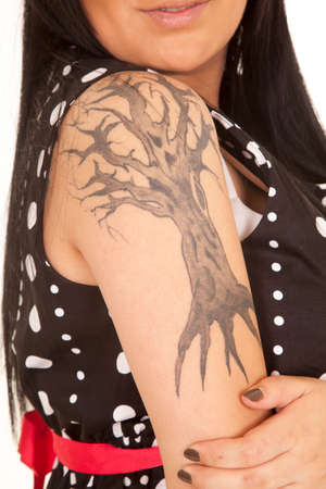 A close up of a womans shoulder with a tree tattoo. photo