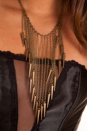 A close up of a womans neck wearing a gold charm necklace. Imagens