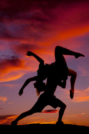 A silhouette of a woman and man dancing in the outdoors, he is lifting her up. Banco de Imagens