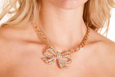 A close up of a blond womans neck wearing her diamond bow necklace. photo