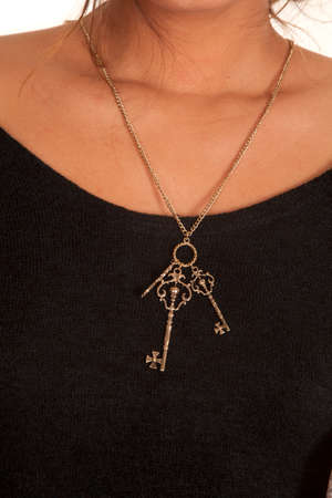 A close up of a woman wearing a necklace that has key charms on it. photo