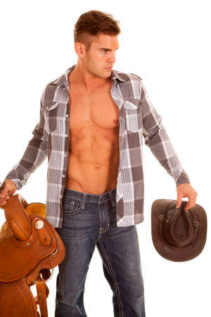 A cowboy holding onto his hat and his sadde with a serious expression.