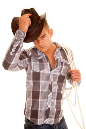 poised: A cowboy in his plaid top and hat with a rope.