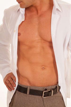 shirt unbuttoned: a man with his white business shirt unbuttoned with his hand on his hip.