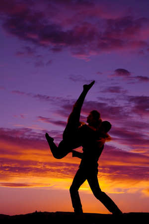 a silhouette of a man lifting up his woman doing a dancing lift. Banco de Imagens