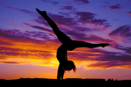 A silhouette of a woman doing a handstand split in the outdoors. photo