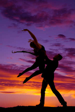 he: A silhouette of a man and woman dancing, he is doing a lift.