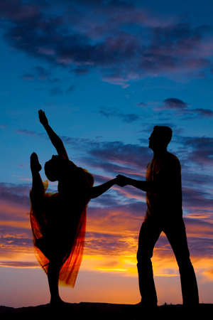 a silhouette of a man and woman dancing, he is holding her hand, while she is lifting her leg.