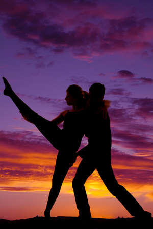 a silhouette of a man and woman dancing, she is leaning back into him while she lifts her leg.