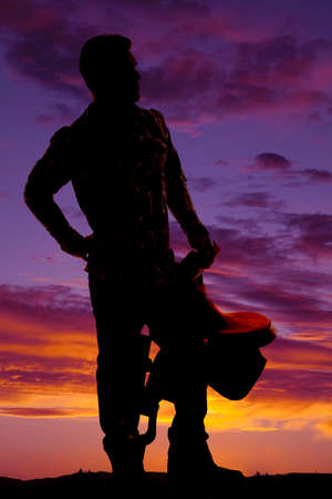 A silhouette of a cowboy holding on to his saddle looking to the side. photo