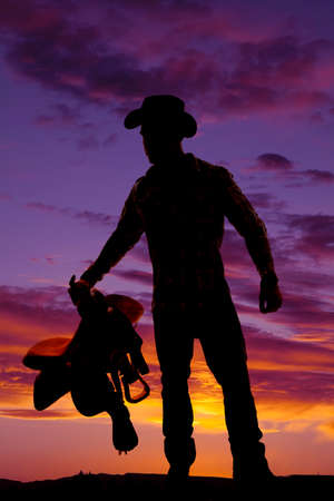 A silhouette of a cowboy in the outdoors, holding on to his saddle. photo
