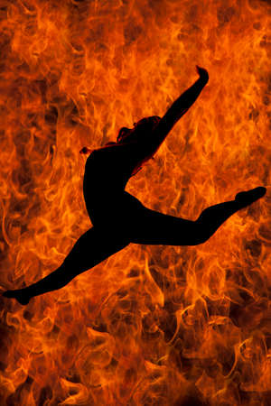 a silhouette of a woman doing a leap with fire behind her.